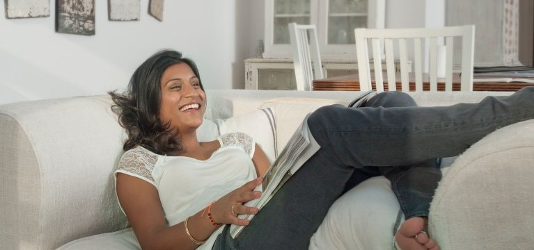 Woman with dark hair laughing and reading a magazine