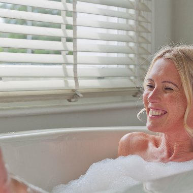 Woman with blonde hair lying in the bathtub smiling