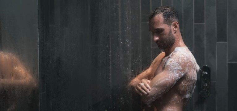 Athletic man lathering and exfoliating his skin in grey slate tiled shower.