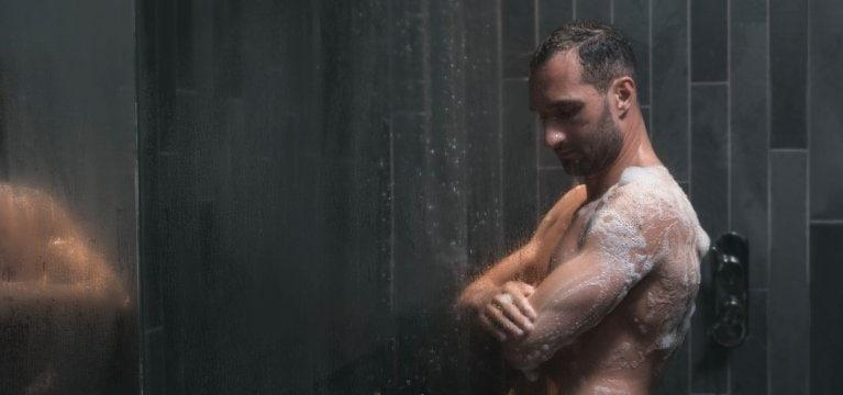 Un athlète fait mousser le savon et exfolie sa peau dans une douche en ardoise grise.