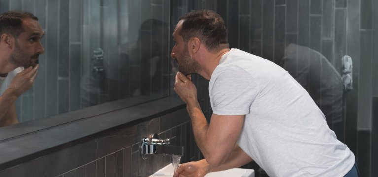 White shirted man in grey slate tiled bathroom looks into the mirror while touching his facial hair.